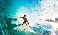 Close-up of a surfer riding a large blue wave