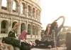 Tourists pose for selfies by the Colosseum in Rome, Italy