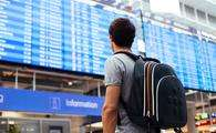 Young man with backpack in airport near flight timetable (Photo via furtaev / iStock / Getty Images Plus)